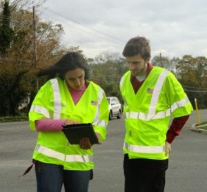 Two staff members in safety vests looking at a digital tablet during a Road safety Audit (RSA)