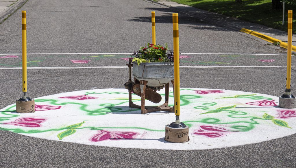 Temporary pop-up roundabout with radius deliniators, decorative street art and flower planter in the center