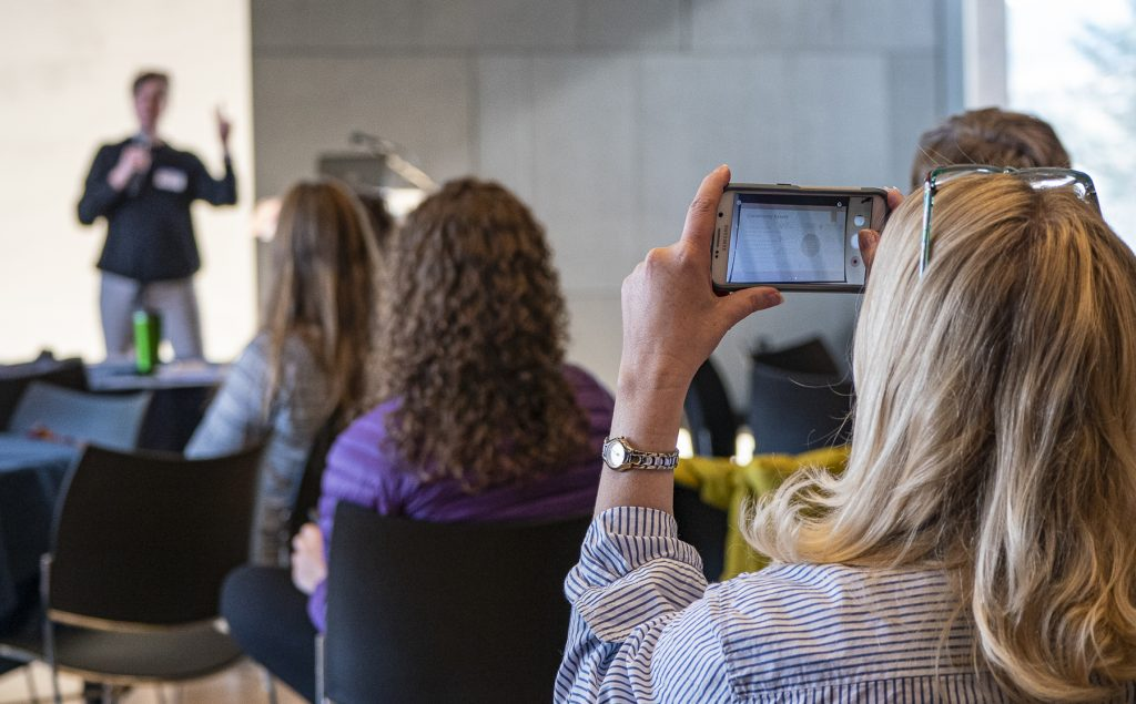 Female member of audience using smartphone to capture images during a community development presentation.