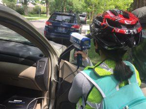Student crouched behind a parked vehicle using a radar gun on an urban street
